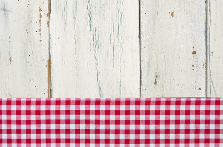 Red checkered tablecloth on a white wooden background photo