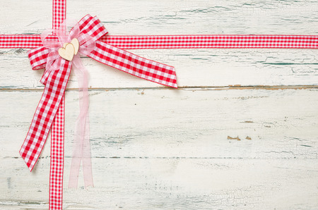 red gingham: Red ribbons and a bow on a white wooden background Stock Photo