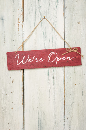 Red sign in front of a white wooden wall - We are open