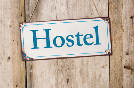 Old metal sign in front of a rustic wooden wall - Hostel
