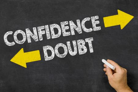 dudas: La confianza o duda por escrito en una pizarra Foto de archivo