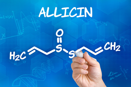 chemical formula: Hand with pen drawing the chemical formula of Allicin