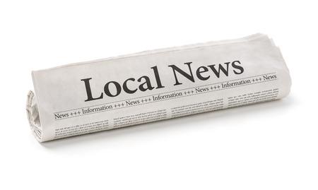 Gerollte Zeitung mit der Schlagzeile Local News Standard-Bild
