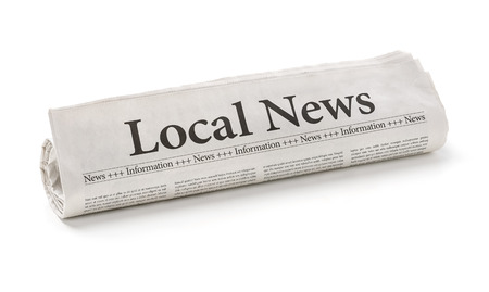 latest news: Rolled newspaper with the headline Local News Stock Photo
