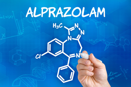 sedative: Hand with pen drawing the chemical formula of Alprazolam