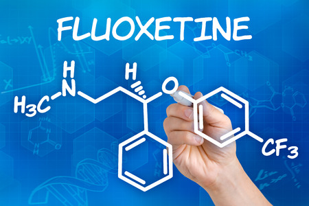 chemical formula: Hand with pen drawing the chemical formula of Fluoxetine