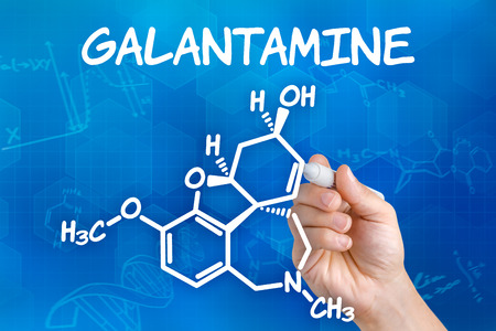 acetylcholine: Hand with pen drawing the chemical formula of Galantamine Stock Photo