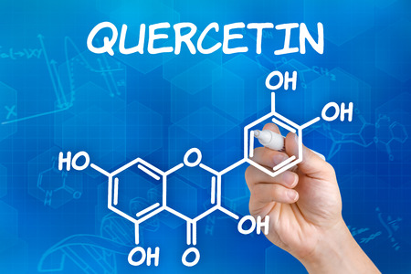 chemical formula: Hand with pen drawing the chemical formula of Quercetin
