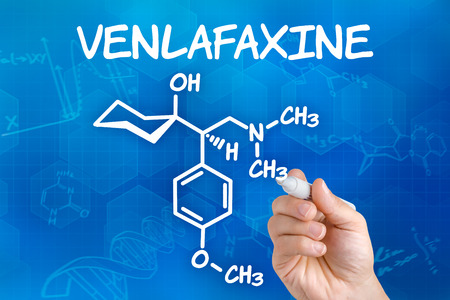 major depression: Hand with pen drawing the chemical formula of Venlafaxine