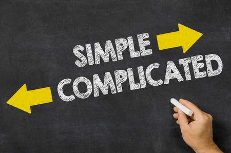 simple: Simple or Complicated written on a blackboard Stock Photo