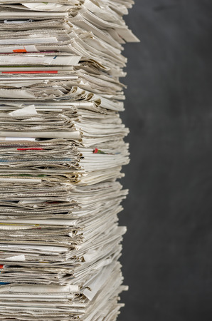 wastepaper: Piled newspapers on a dark background