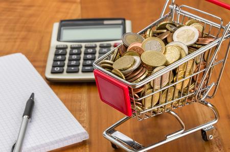 Nákupní košík plný mince na dřevěný stůl
