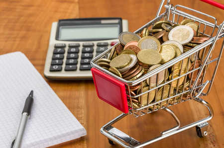 Shopping cart filled with coins on a wooden desk photo