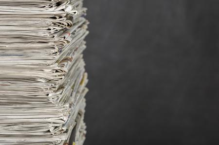 Ein Stapel von Zeitungen vor einer Tafel