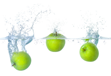 Fresh apples falling into water with splashes