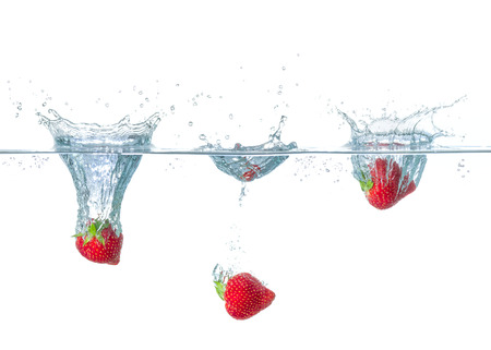 droplets: Fresh strawberries falling into water with splashes