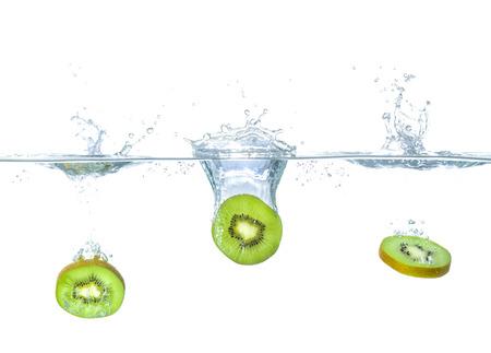 Čerstvé kiwi spadající do vody s postříkání