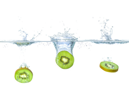 Fresh kiwis falling into water with splashes Stock Photo