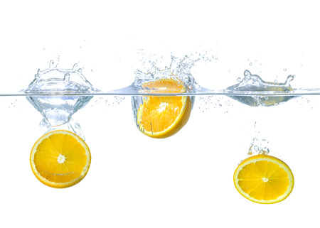 Fresh oranges falling into water with splashes