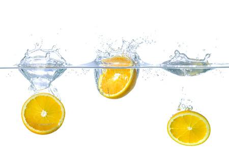 Frische Orangen fallen ins Wasser mit Spritzern