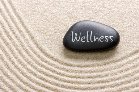 A black stone with the inscription Wellness Stock Photo
