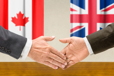 foreign policy: Representatives of Canada and the UK shake hands