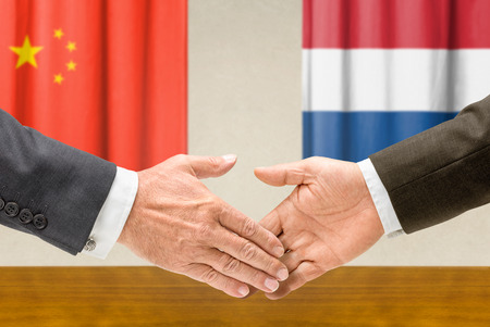 Representatives of China and the Netherlands shake hands Stock Photo