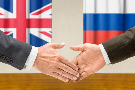 foreign policy: Representatives of the UK and Russia shake hands Stock Photo