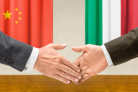 china: Representatives of China and Italy shake hands