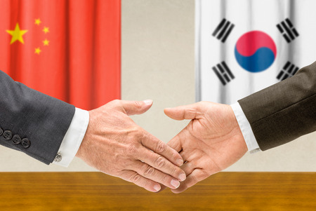 foreign policy: Representatives of China and South Korea shake hands