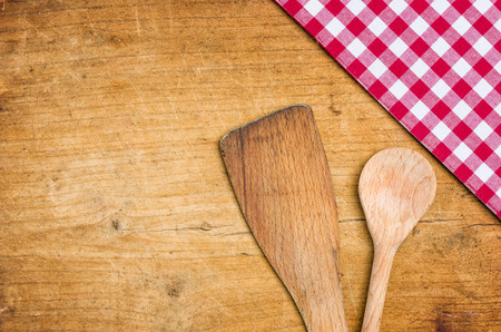 menue: Wooden spoon with a checkered tablecloth on a wooden background Stock Photo