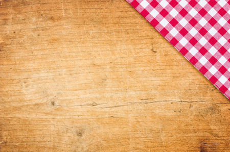 A wooden background with a checkered tablecloth Stock Photo