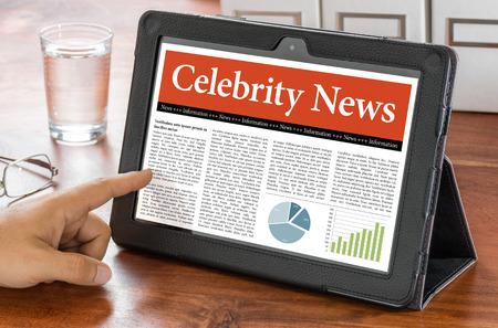celebrity: A tablet computer on a desk - Celebrity News Stock Photo