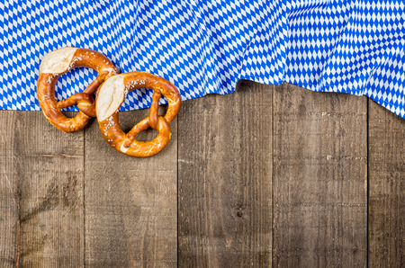 menue: Wooden boards with a bavarian diamond pattern and pretzels Stock Photo