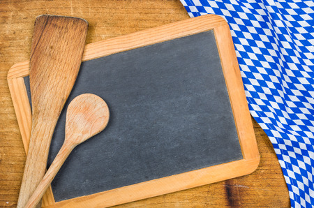 menue: Wooden spoons and chalkboard with a bavarian tablecloth
