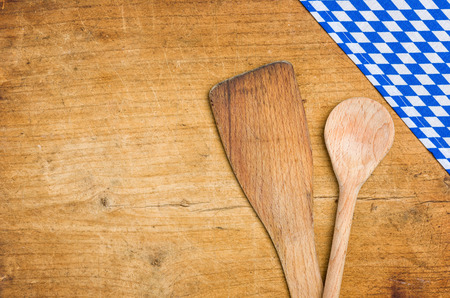 menue: Wooden spoons with a bavarian tablecloth on a wooden background