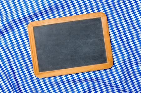 menue: Empty blackboard on a bavarian diamond pattern Stock Photo
