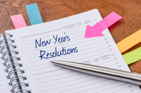 new year: Daily planner with the entry New Years Resolutions Stock Photo