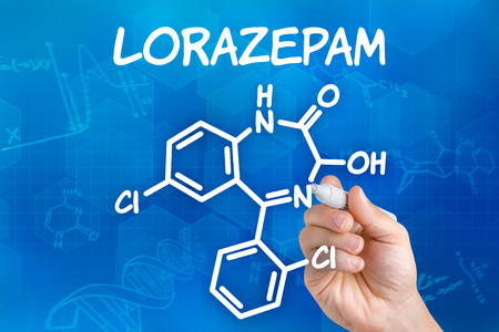 nausea: Hand with pen drawing the chemical formula of Lorazepam