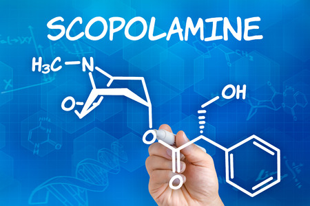 chemical formula: Hand with pen drawing the chemical formula of Scopolamine