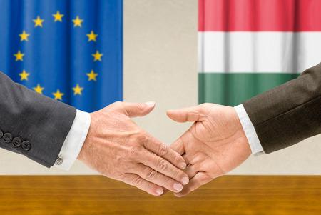 representatives: Representatives of the EU and Hungary shake hands Stock Photo