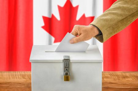plebiscite: Man putting a ballot into a voting box - Canada