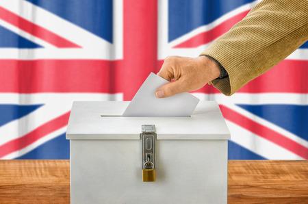 Man putting a ballot into a voting box - United Kingdom