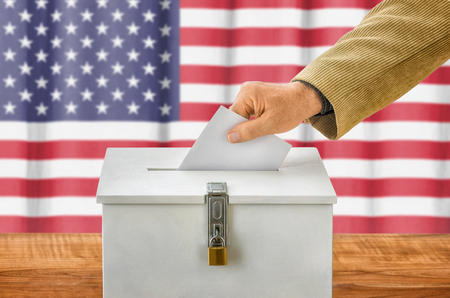 Man putting a ballot into a voting box - USA Stockfoto