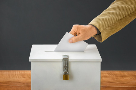 politics: Man putting a ballot into a voting box