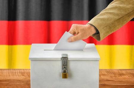 balloting: Man putting a ballot into a voting box - Germany Stock Photo