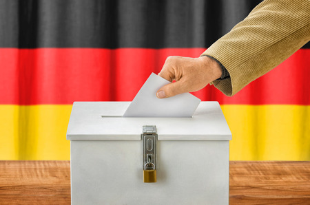 Man putting a ballot into a voting box - Germany Stock Photo