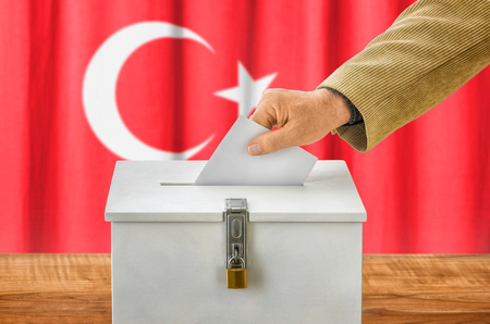 state election: Man putting a ballot into a voting box - Turkey