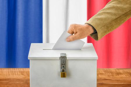 Mann, der einen Stimmzettel in eine Wahlurne setzen - Frankreich