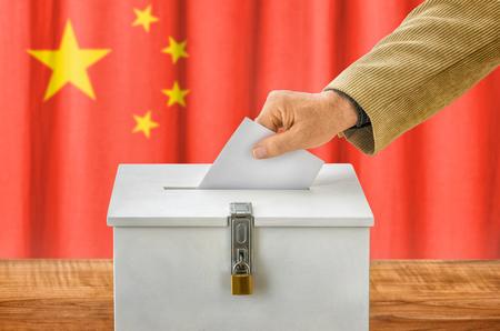 voting box: Man putting a ballot into a voting box - China